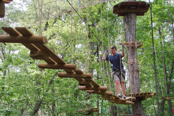 A man walks along one of Treetop Quest's lifted bridges.